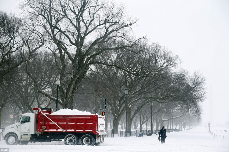 A pedestrian waits to cross the street as a truck carrying a load of snow passes in front on the National Mall in Washington