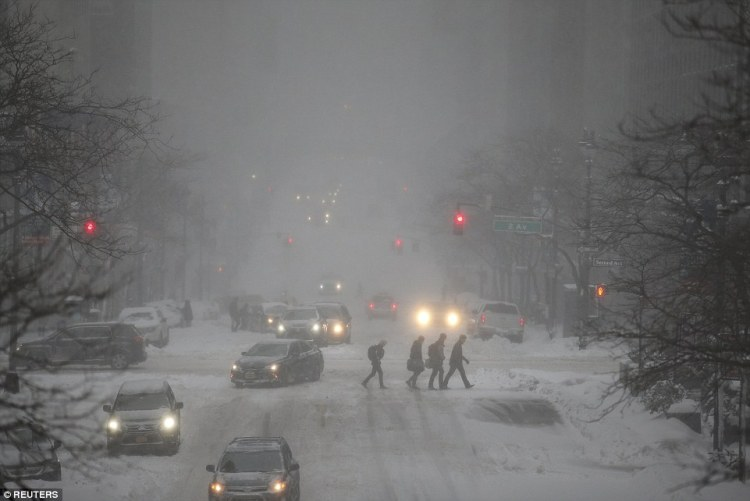 People trudge though the snow as they cross 42nd St during a snowstorm Manhattan borough of New York