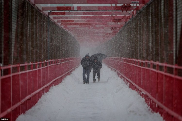 People walk across the Williamsburg Bridget during a large winter storm in the Williamsburg section of Brooklyn, New York, on Saturday