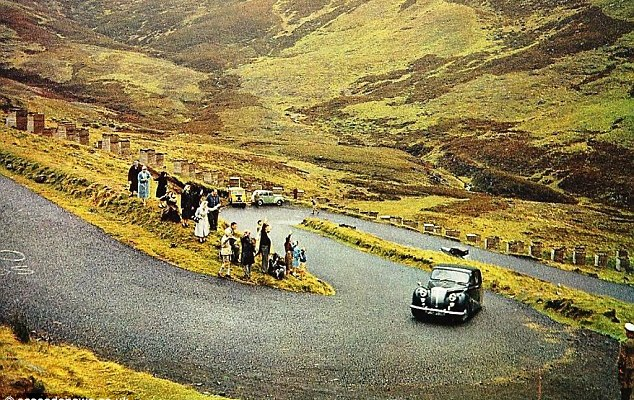 Crowds watch Queen Elizabeth II being driven along The Devil's Elbow to Balmoral by Prince Philip in 1967