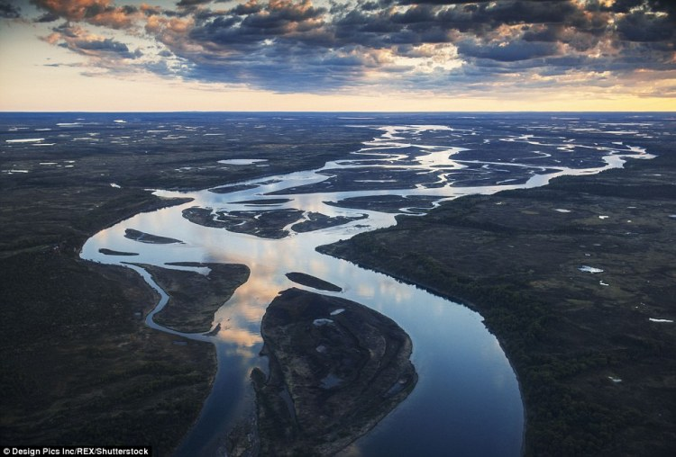 An aerial view of the Kvichak River with numerous split channels in Southwestern Alaska reflects the clouds above