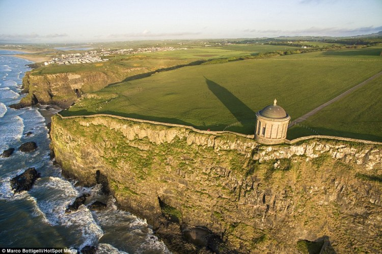 As the evening hours close in the light softens and the shadows of The Mussenden Temple in County Londonderry (above), Northern Ireland, lengthen