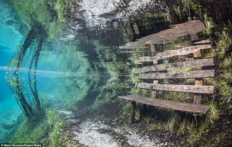 A bench, usually used by visitors wishing to enjoy the stunning surrounding landscape, is submerged in freezing cold water