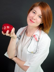 Dr. Laura Nurse Naturopathic Doctor holding an apple