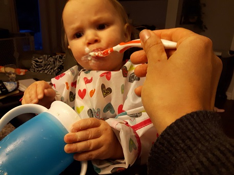 spoon feeding toddler goat cheese for a parenting win
