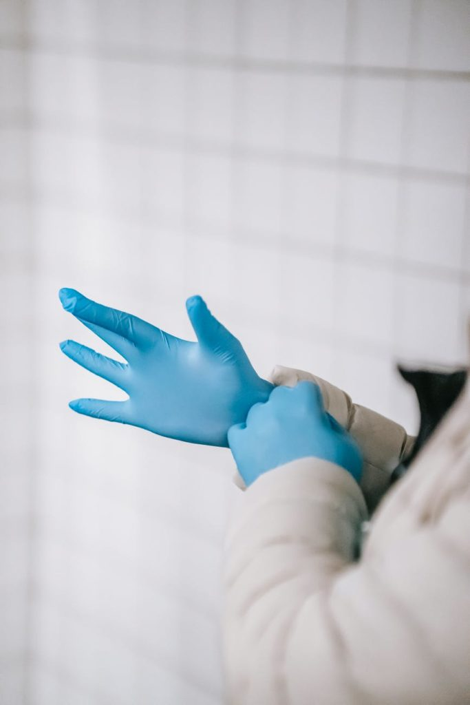 crop faceless person in outerwear putting on latex gloves