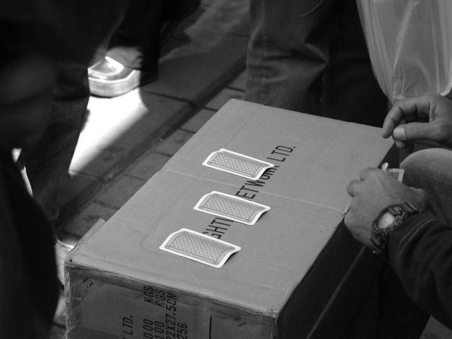 Three Card Monte game on a cardboard box