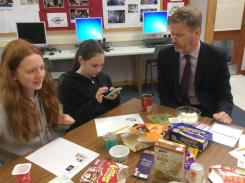 Mr O'Neill helps pupils use an app on their phones to use barcodes to list the amount of sugar in products