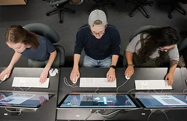 A view from above of three graphic design students working on computers.