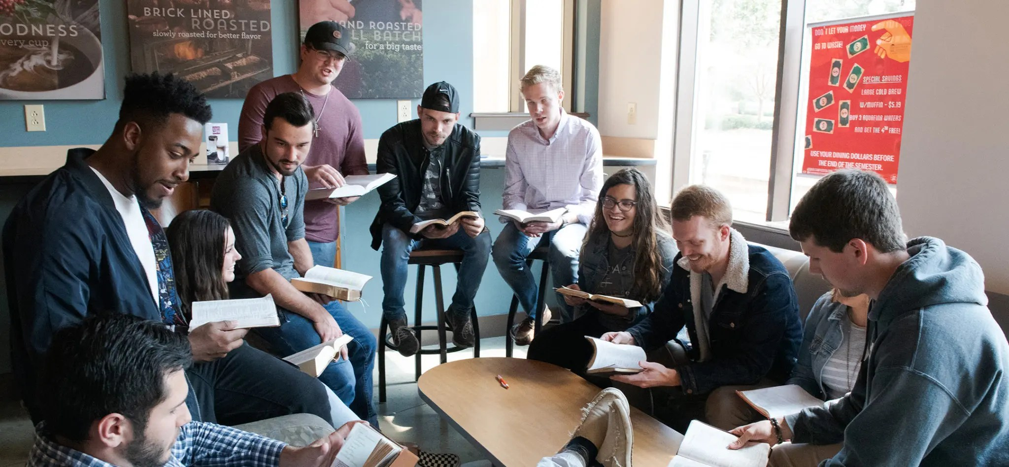 A group of students in CSU's Java City reading and discussing the Bible.