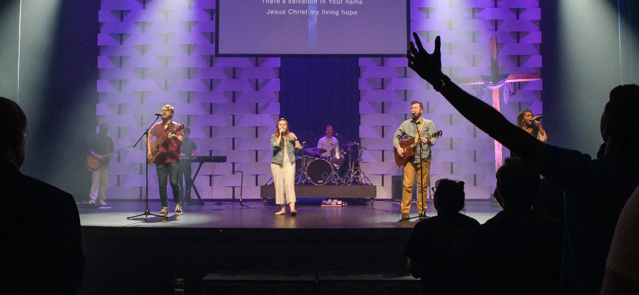 A worship service at Charleston Southern University with a student in the audience raising his arms up in praise.