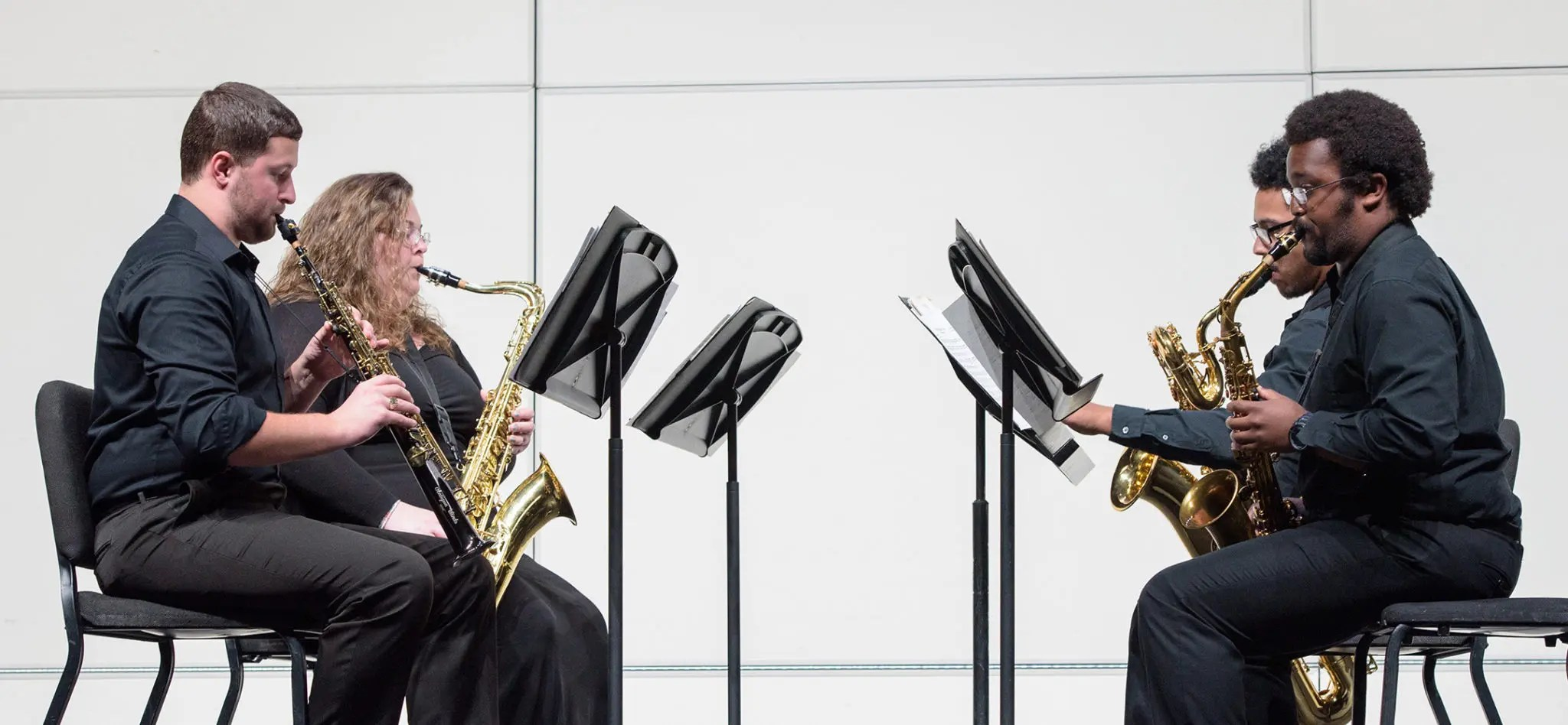 Four students performing a recital with a variety of saxophones.