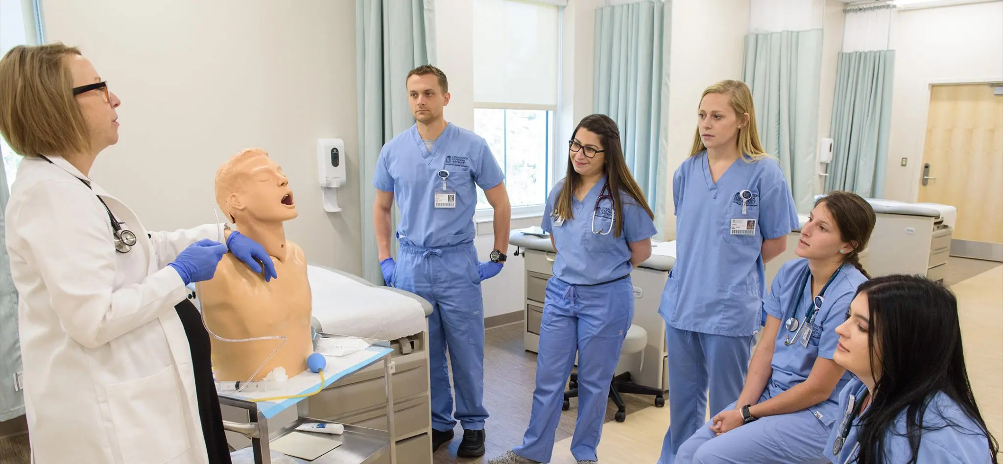 Physician Assistant students in a classroom lab listening to a professor explain how to insert a tube into a human dummy.