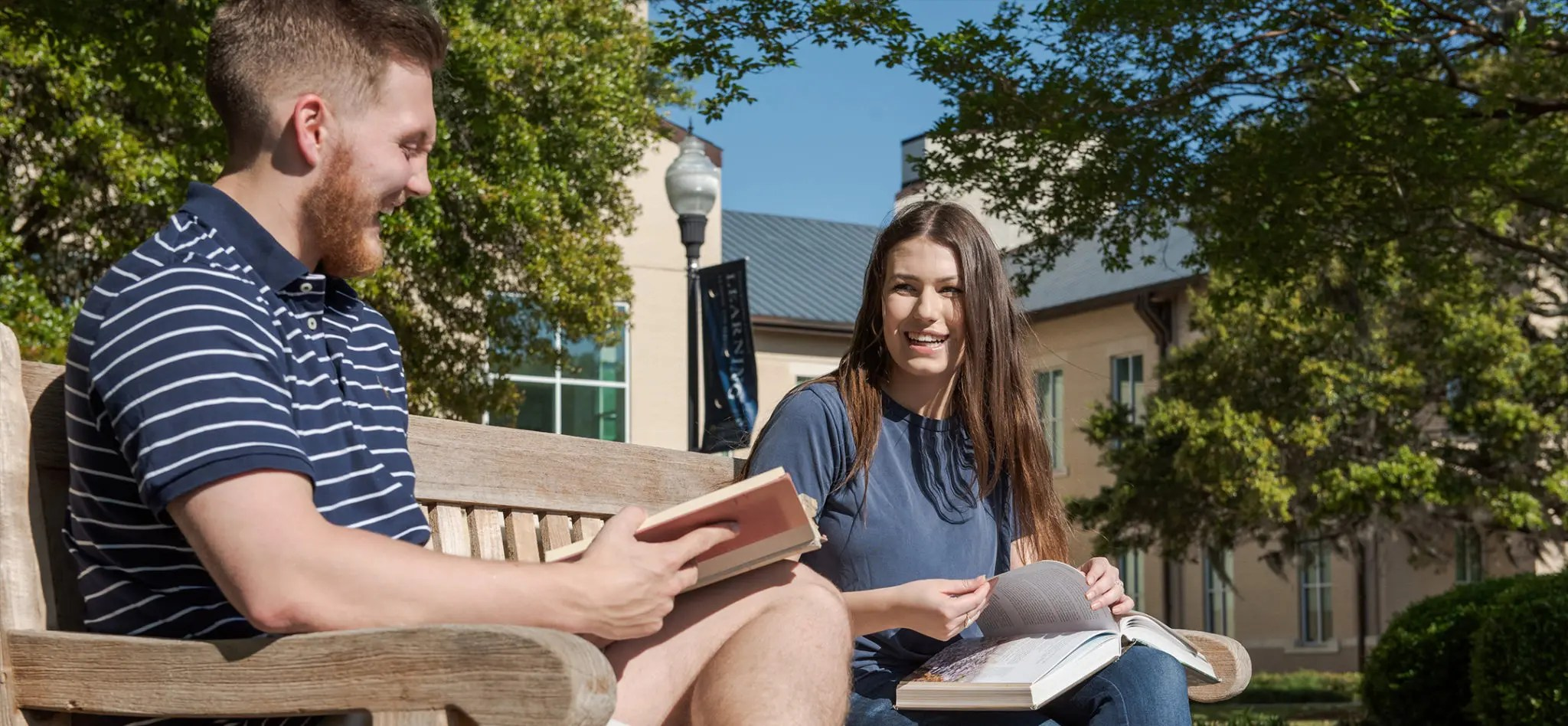 Two students sitting on a bench outside discussing their classwork with books in hand.