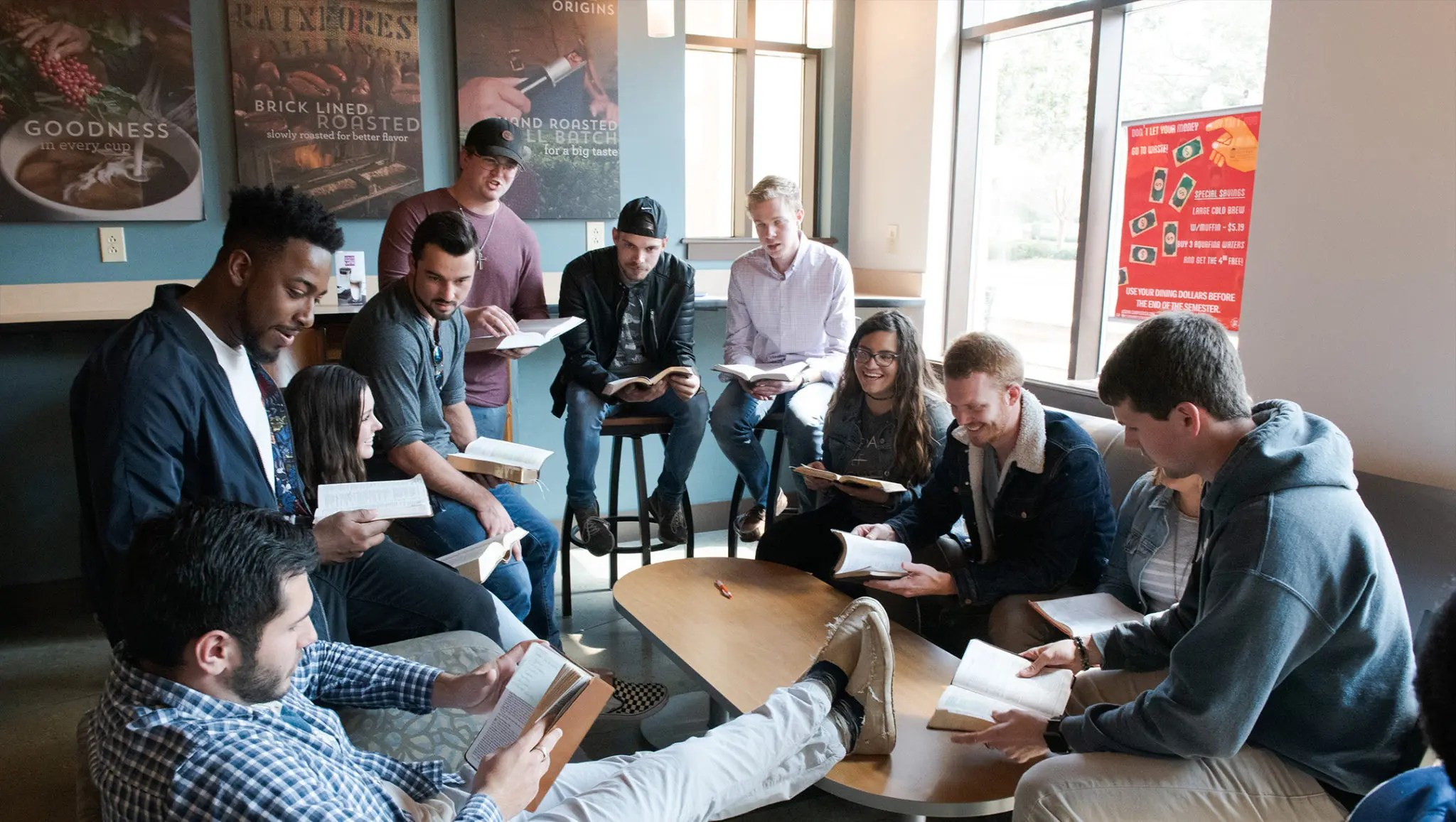 Students gathered around a coffee table in a coffee shop looking through their bibles and in discussion.
