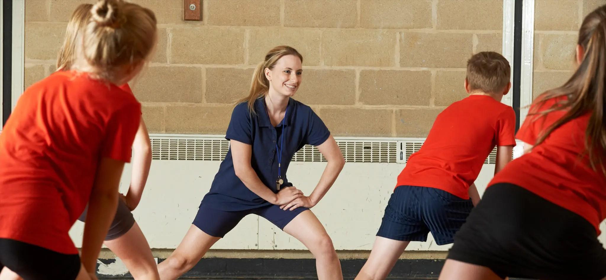 Teacher giving an exercise class in a school gym.