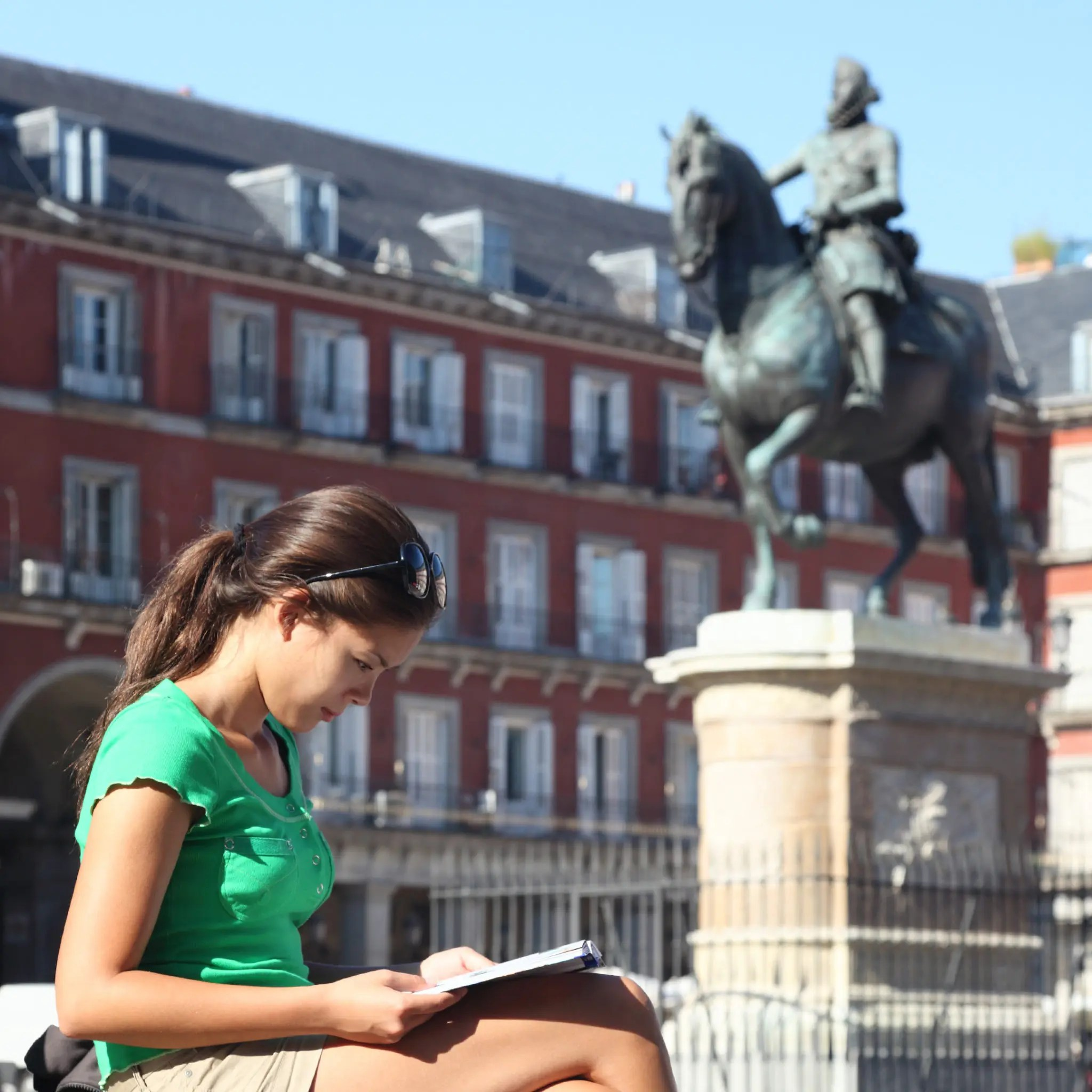 In Madrid, Spain, a woman tourist looking at a notebook on Plaza Mayor in summer with a statue behind her.