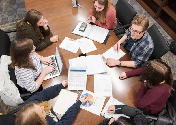 An overhead view of students around a table with papers containing charts and graphics.