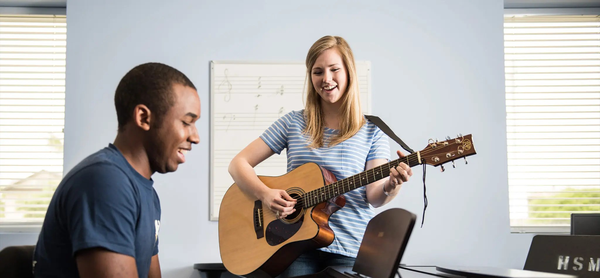 Two music therapy students playing music together. One with a guitar and the other on a piano.