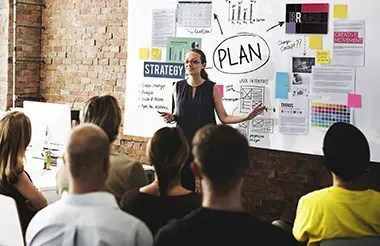 A woman at a whiteboard going over a marketing plan with her team.
