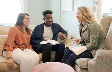 A college minister talking with two college students in a college dorm.