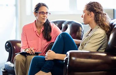 Female psychologist having session with a young female patient.
