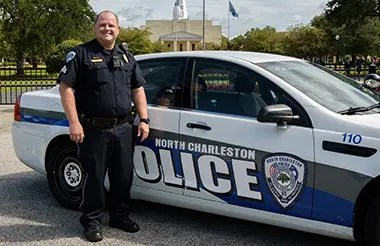 A police officer stands in front of a north charleston police car parked on the CSU campus.