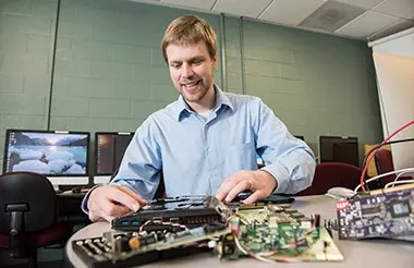 An adult student taking apart a laptop computer in a computer lab.