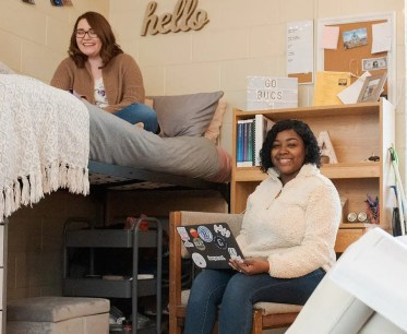 Three students in a female dorm room talking and studying together.