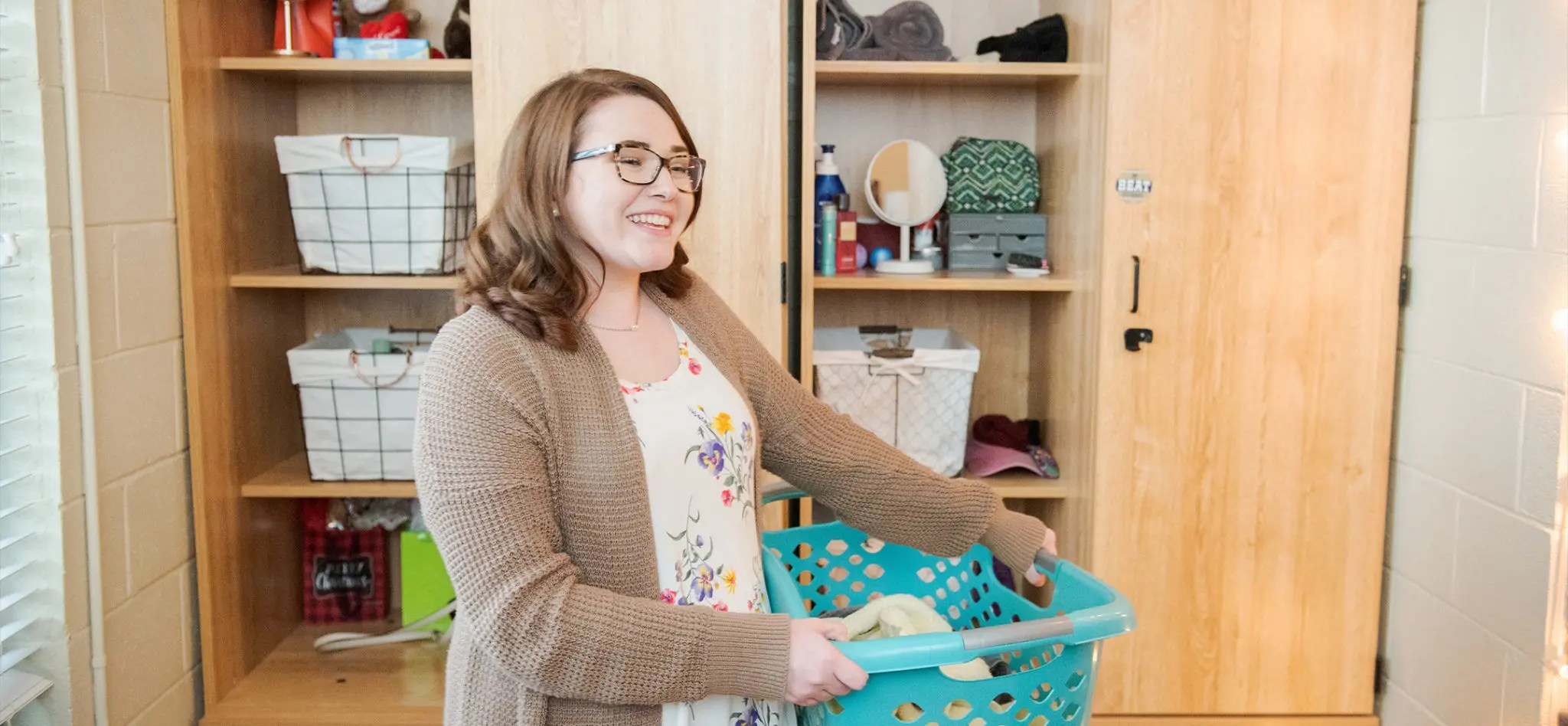 A female student in her dorm room with a basket of laundry in her arms and storage cabinets behind her.