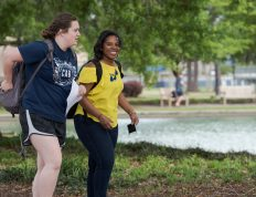 Two students walking around the reflection pond at CSU while on their was to class.