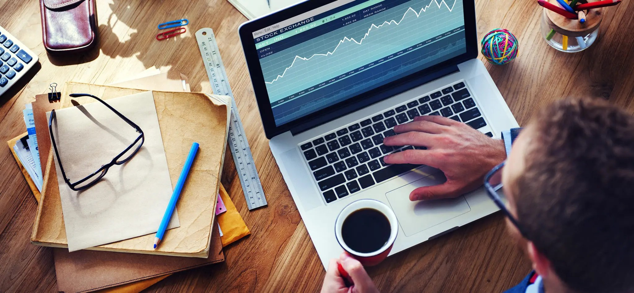 Looking down at a man on a computer with stock market information on the screen. His desk is covered with papers and other items.
