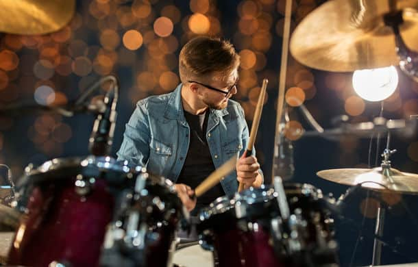 Music Musical Instruments And Entertainment Concept Male Musician With Drumsticks Playing Drums And Cymbals At Concert Or Studio Over Holidays Ligh