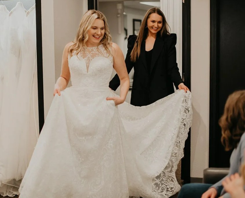Helping bride in her wedding dress
