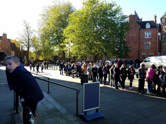 Long line to enter The Minster in October sunshine.