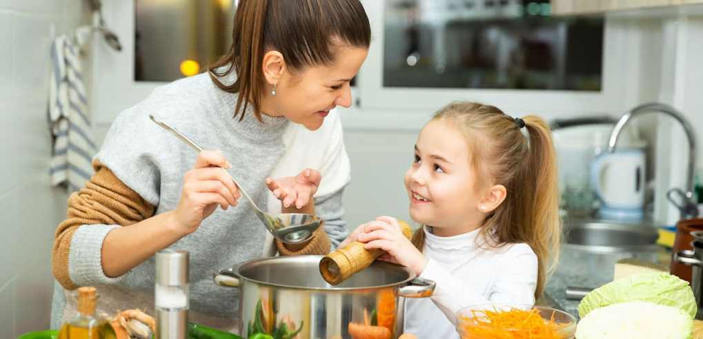 Mom and daughter making soup
