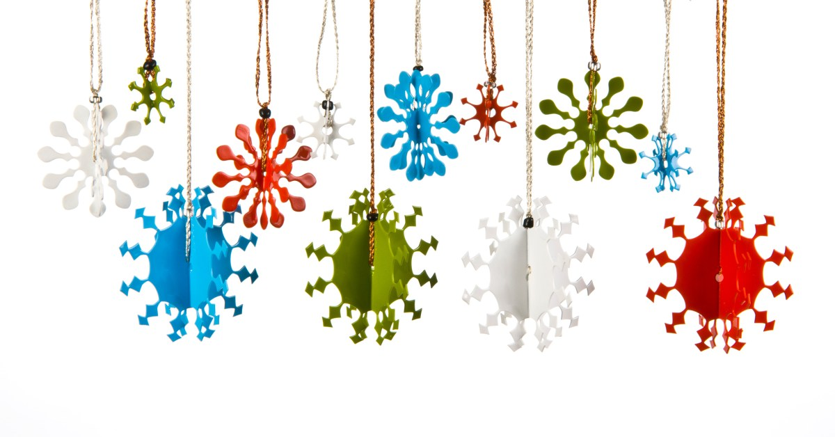 A collection of 3D metal snowflakes, some small, some medium and some large, coated in different coloured enamel paint each with a thread for hanging on the Christmas tree.