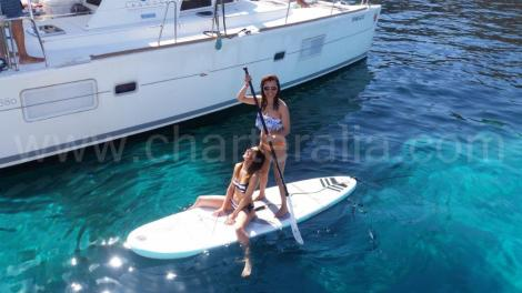 Menina no paddleboard ao lado do catamara em Ibiza