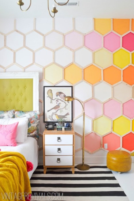 A bedroom wall with wooden sticks making a honeycomb pattern on it.