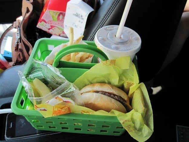 A green dollar store basket holding fast food in a car.