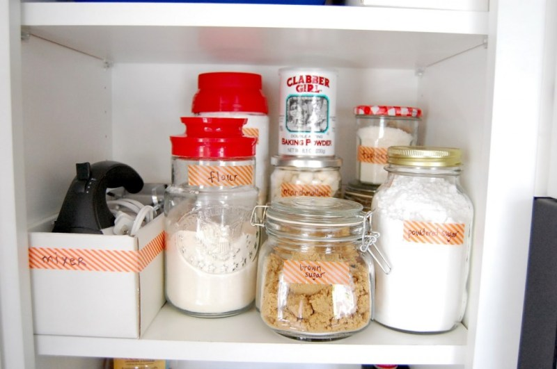 A baking cabinet filled with jars, tins and boxes organized with labels.