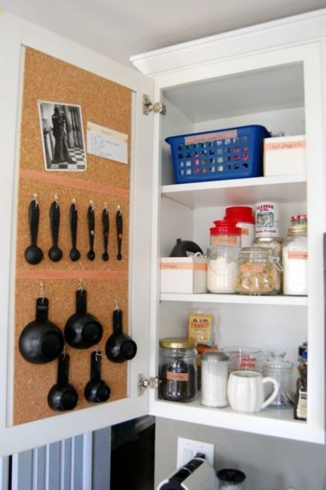 A cork board cabinet door with hooks hanging up measurement cups.