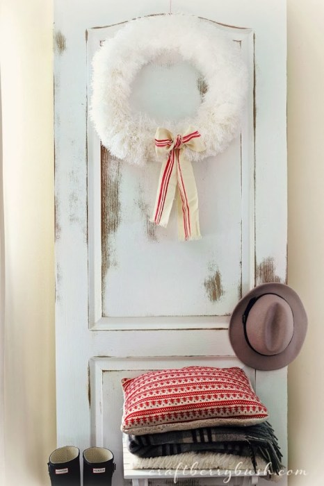 Dusters round together to form a duster wreath attached to a door with a ribbon attached.