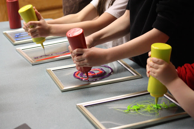 Children squirting paint from bottles onto transparent picture frames.