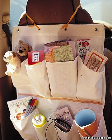 A pale brown shoe organizer filled with goodies overhanging on the back of a car's front seat