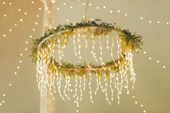 A homemade hula hoop chandelier wrapped in garlands and LED lights.