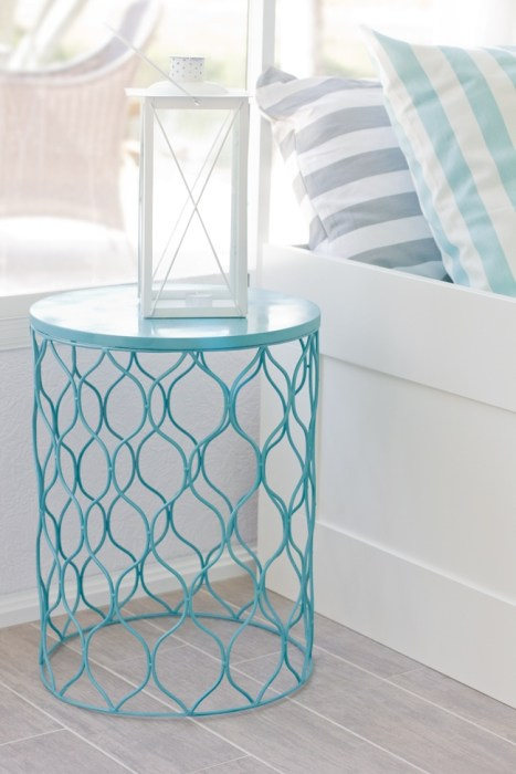 A trash can turned upside down and painted blue to use as a side table.