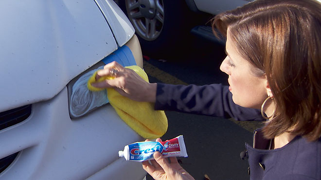 Dabbing toothpaste with a cloth onto a car's front headlight
