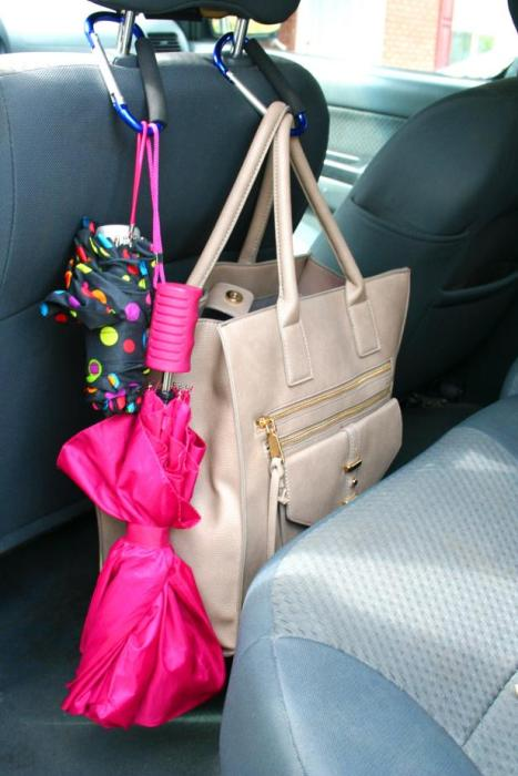Two carabiners holding up two umbrellas and a bag attached to a headrest overhanging the back of the front seat