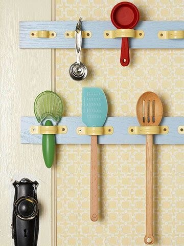 Utensils hung up on a door using pipe fittings.